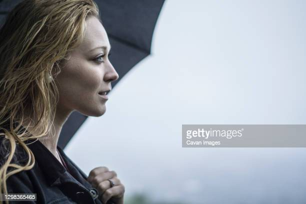blonde female fashion model discovering city in the rain - damp lips stock pictures, royalty-free photos & images