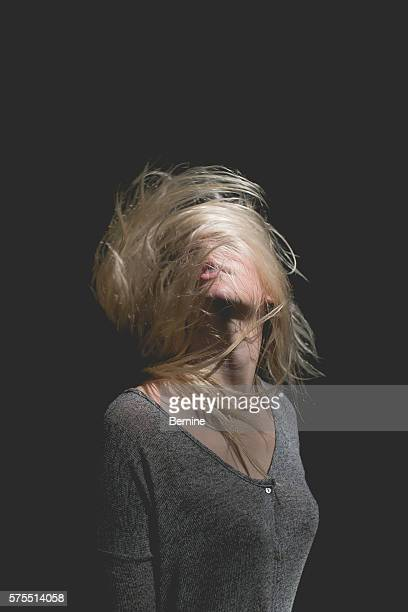 blonde female with hair whipping over face - 頭をそらす ストックフォトと画像