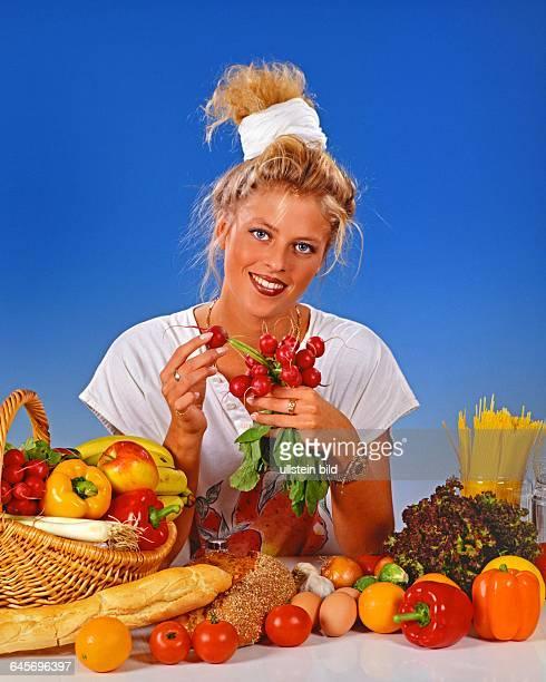 Blonde Frau isst Radieschen zum Fruehstueck,