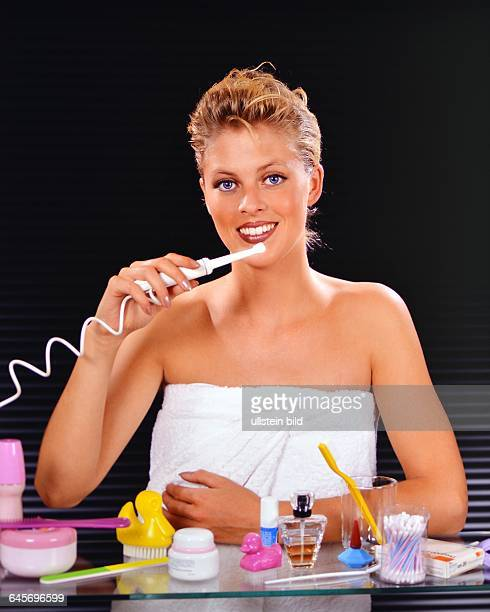 Blonde Frau putzt sich die Zaehne, Kein Modelrelease