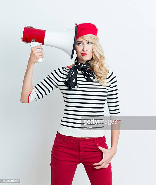 Blonde french woman wearing red beret holding a megaphone