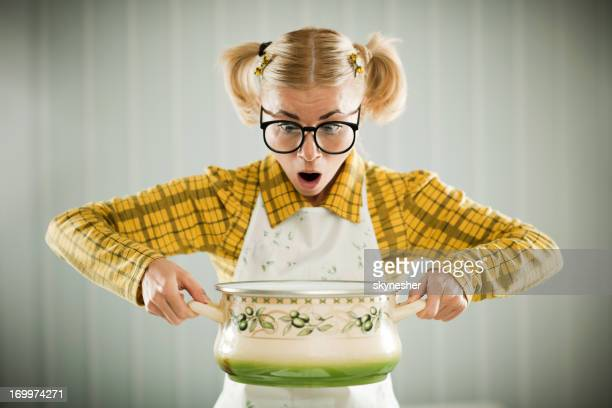 Blonde geek holding cooking pot.