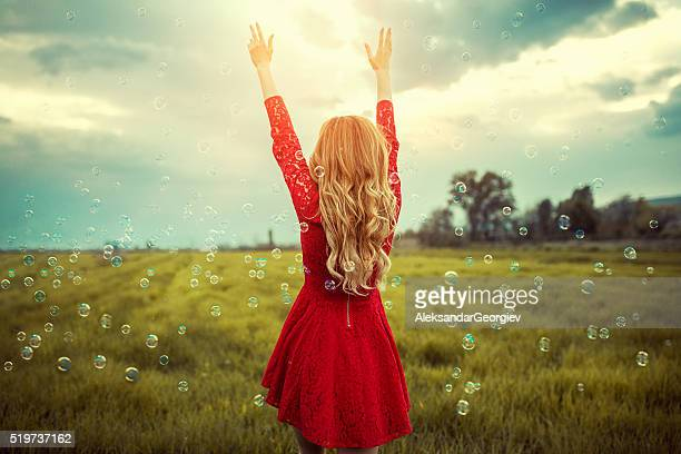 Blonde Girl Enjoying Nature with Spread Arms Surrounded with Bubbles