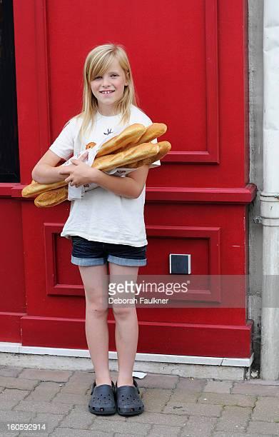 Blonde girl holding baguettes under arm