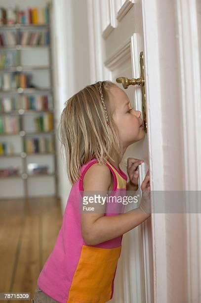 Blonde Girl Peeping Through Keyhole of Door
