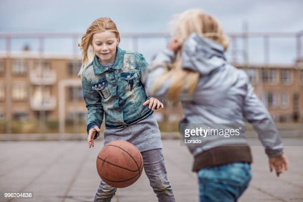 blonde girl playing basketball on a streetball court - offspring stock pictures, royalty-free photos & images