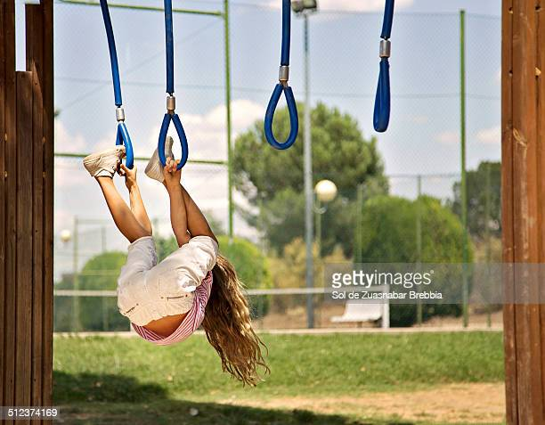 Blonde girl playing, hanging upside down in a park