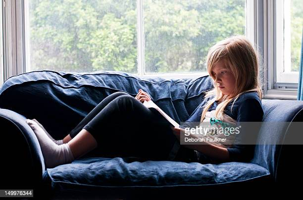 blonde girl reading book - little girls socks stock photos and pictures