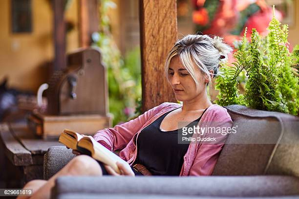 blonde girl relaxing reading book in cozy lounge