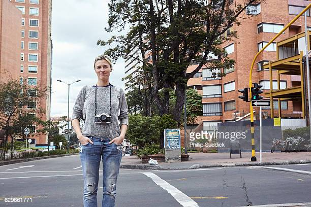 blonde girl taking with film camera in a city