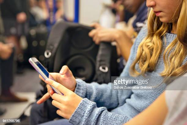 blonde girl texting while traveling on a subway - kin in de hand stock pictures, royalty-free photos & images