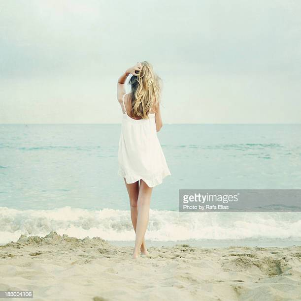 Blonde girl walking towards the sea