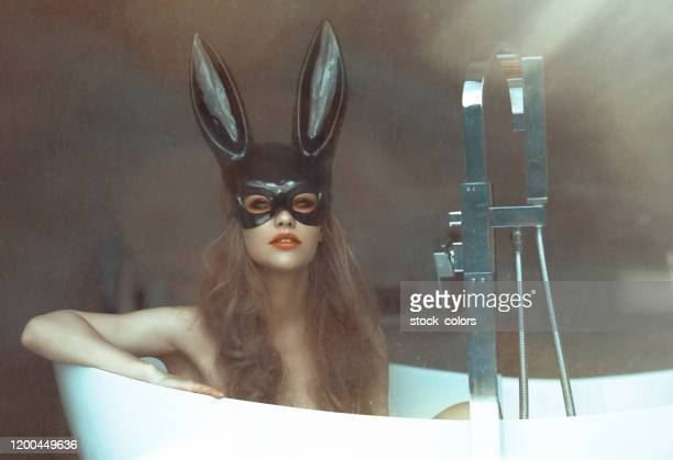 blonde girl wearing bunny mask in the... bathtub?! - rabbit mask stock pictures, royalty-free photos & images