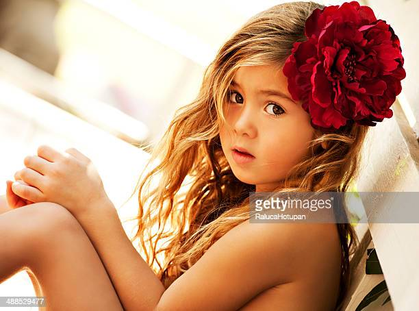 blonde girl wearing red flower in her hair