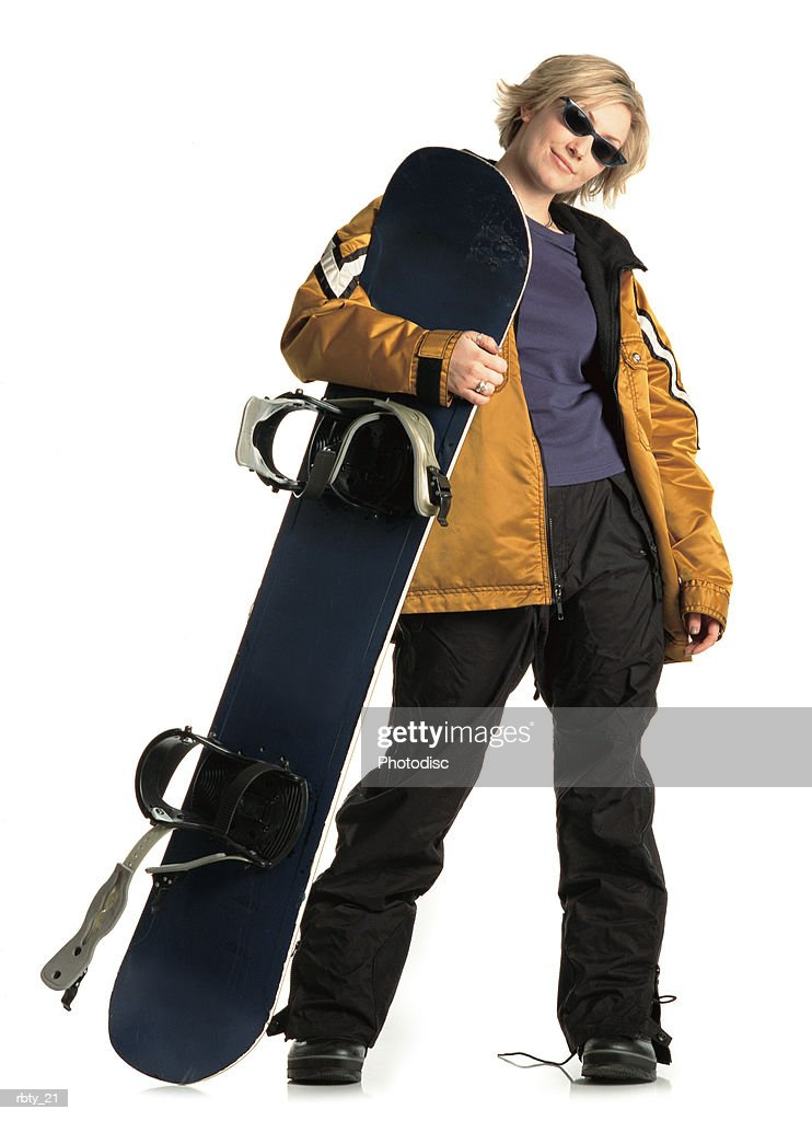blonde girl with an attitude wearing a purple shirt yellow jacket and black snowpants smiles at the camera as she holds her snowboard and looks through her sunglasses : Foto de stock
