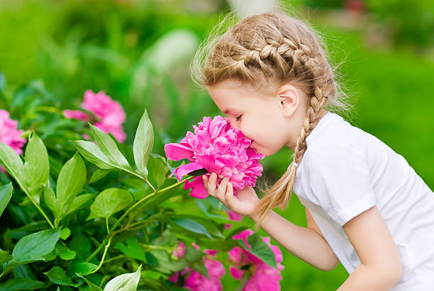 Blonde girl with braided hair smelling pink flower in garden