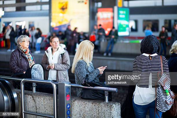 Blondine Mädchen mit Handy im Bahnhof