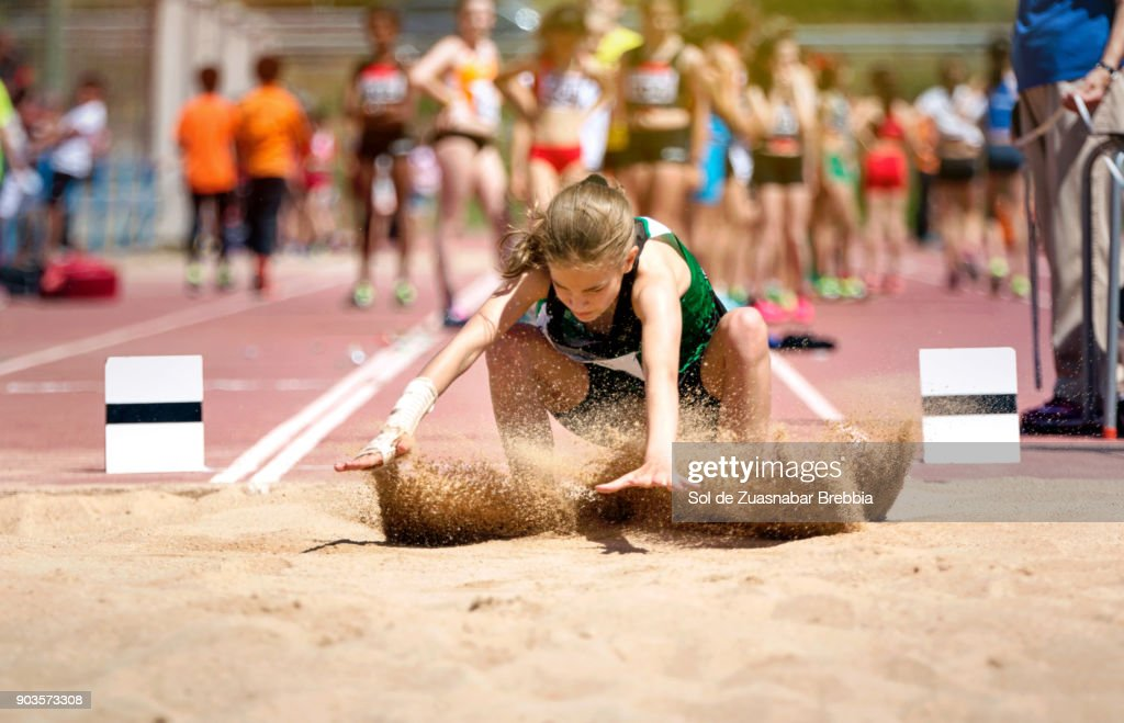 Blonde girl with pigtail landing on the sand in long jump : Stock Photo