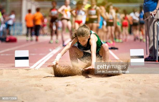 Blonde girl with pigtail landing on the sand in long jump