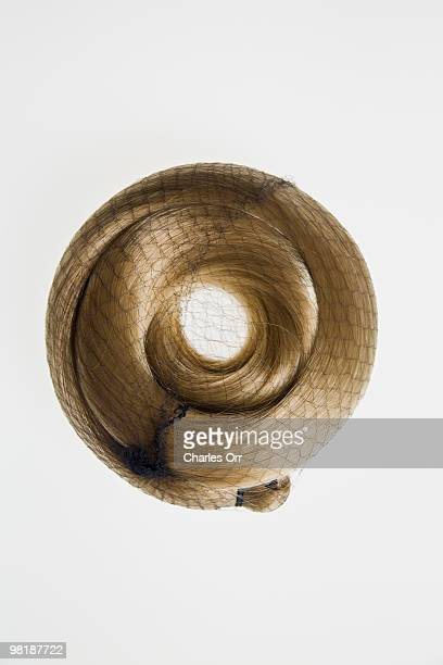 A blonde hair piece curled up in a net