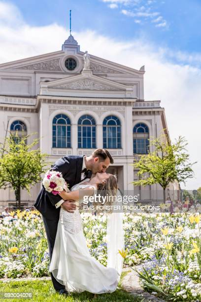 blonde haired bride in wedding dress with long veil and with the bridal bunch of flowers consisting of white and pink peony flowers in her left hand and groom in wedding suit kissing in front of the church short after the wegging ceremony on a sunny day