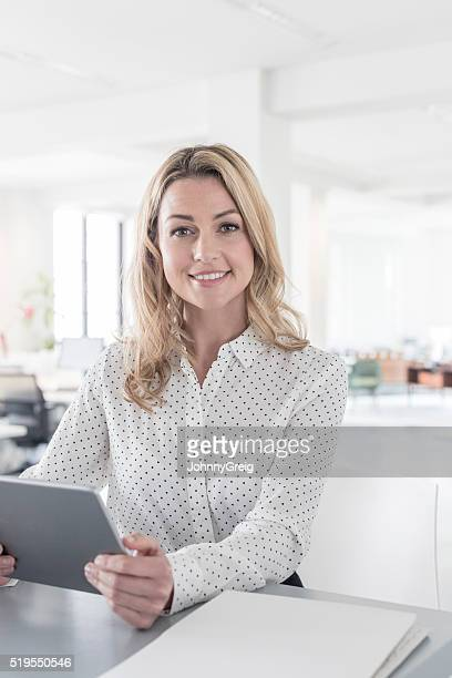 Blonde haired businesswoman with tablet in modern office
