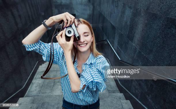 blonde haired girl shooting on old fashioned camera - camera girls - fotografias e filmes do acervo