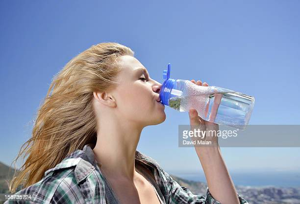 Blonde haired woman drinking water from a bottle.