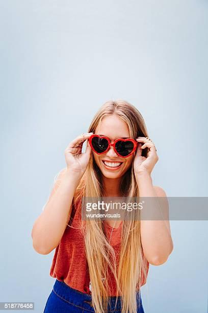 Blonde happy teenage girl with heart sunglasses