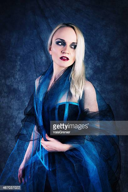 Blonde in blue and black tulle looking away with apprehension.