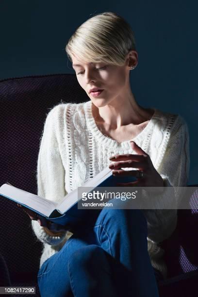dame blonde relaxante avec un livre - tricoté photos et images de collection