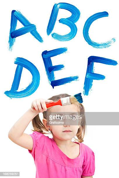 Blonde little girl painting with blue ABC on window