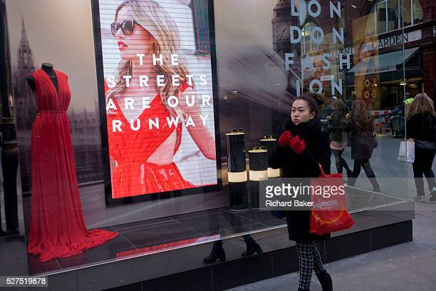 Blonde model shown on a video loop in a central London shop window in the runup to London Fashion Week On a busy street corner in central London's...