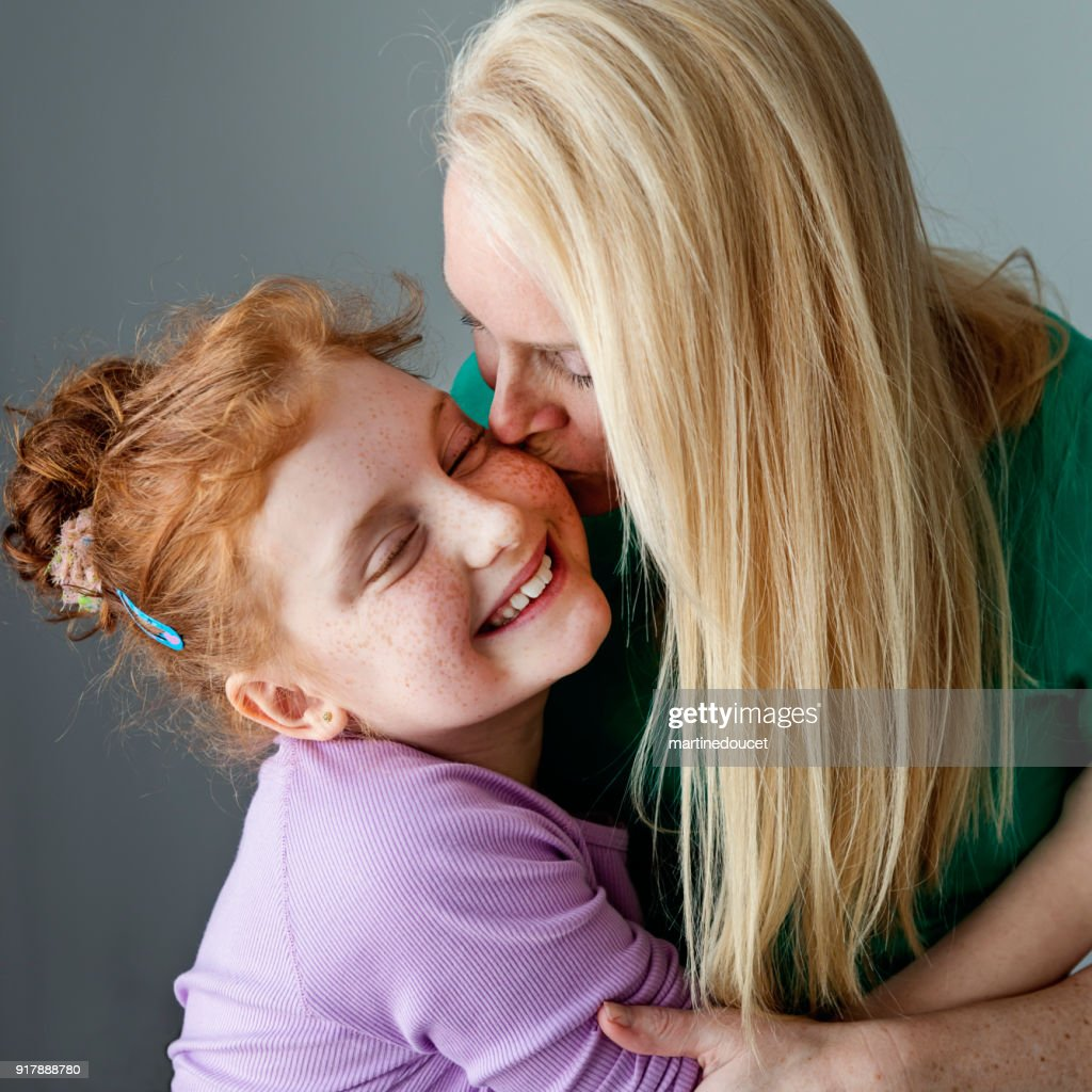 Blonde mother and expressive preteen redhead daughter portrait. : Stock Photo