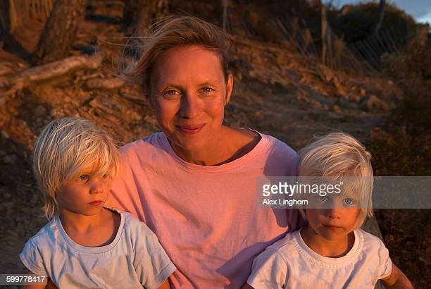 Blonde mother with identical twin boys at sunset