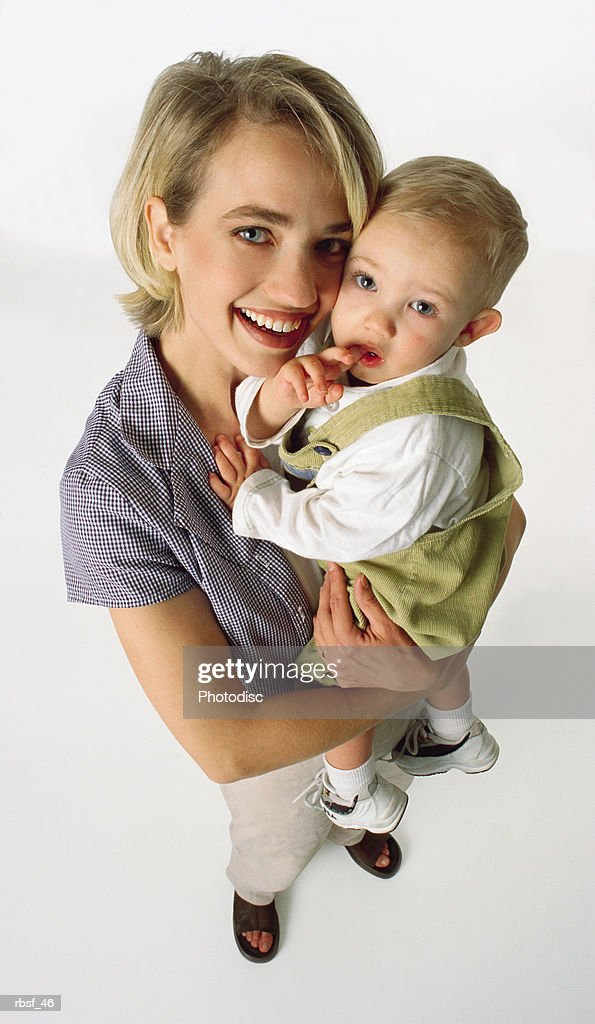 blonde preppy mom smiles and holds her infant : Foto de stock