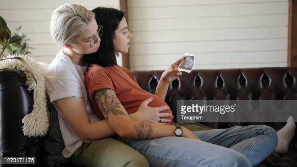 blonde runs hands on pregnant girlfriend belly at home - new life stock pictures, royalty-free photos & images