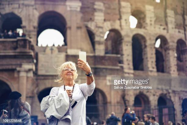 Blonde senior woman making a selfie in front of the roman coliseum