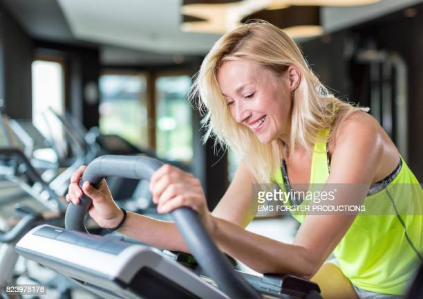 blonde sporty woman while fat burning and cardio training on a modern ergometer exercising bike - ems forster productions stock pictures, royalty-free photos & images