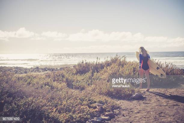 Blonde surfer woman walking at the beach
