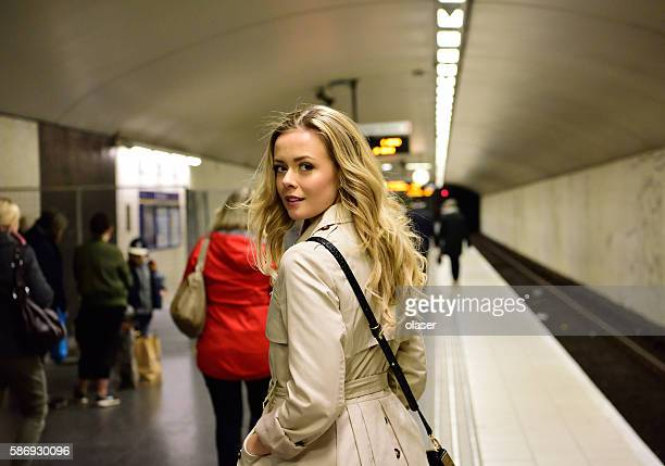 Blonde Swedish woman walking along commuter subway train platform
