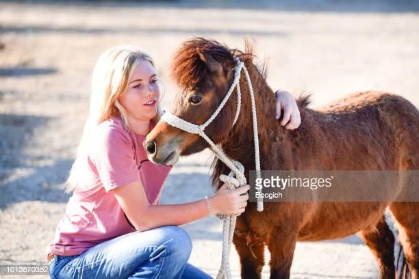 blonde teenage girl hugs her miniature pony in spanish fork utah usa - spanish fork utah stock pictures, royalty-free photos & images