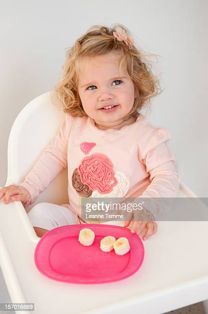 blonde toddler eating a banana - plastic plate stock photos and pictures