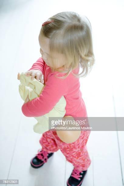 Blonde toddler girl holding baby doll upside down