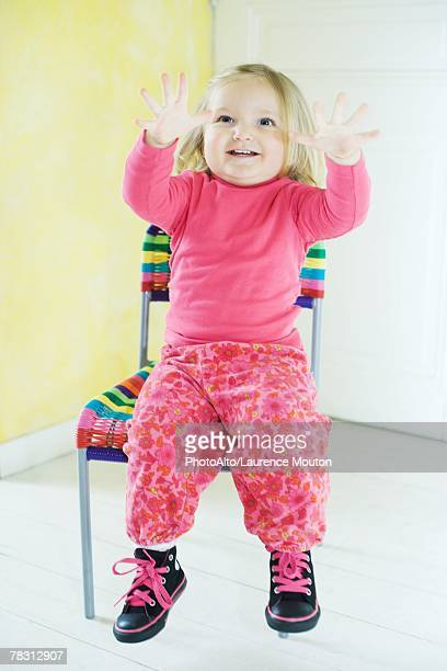 Blonde toddler girl sitting in chair, holding up fingers
