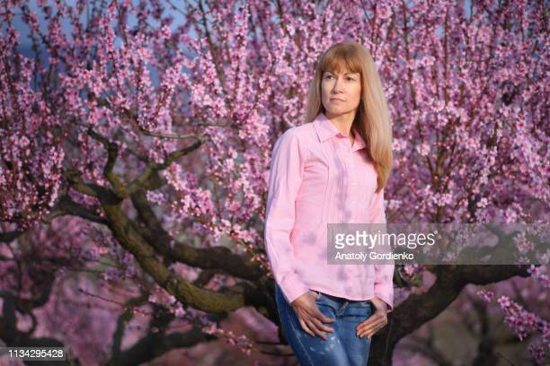 blonde with long hair in pink blouse on background of blooming garden, flowering peach trees. - pink dress stock pictures, royalty-free photos & images