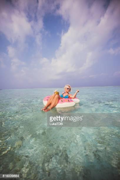 Blonde Frau chillen und schwimmt auf aufblasbaren Donut im Ozean, Malediven