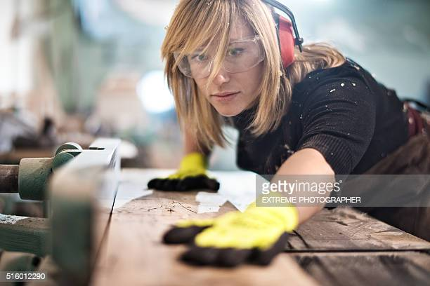 blonde woman cutting a plank - arbeider stockfoto's en -beelden