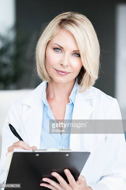 Blonde Woman Doctor in Office with Clipboard