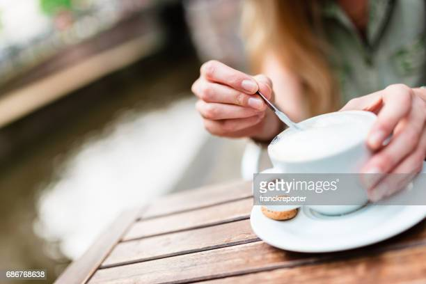 Blonde woman drink a cappuccino at the cafe